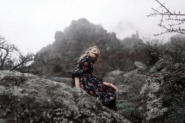 Ulyana Naydenkova GIRL IN FLORAL DRESS SITTING ON FOGGY CLIFF Children