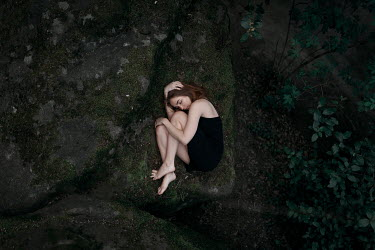 Ulyana Naydenkova BAREFOOT GIRL HUDDLED ON ROCK FROM ABOVE Women