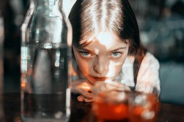 Ulyana Naydenkova STARING GIRL BEHIND SUNLIT BOTTLE AND GLASS Children