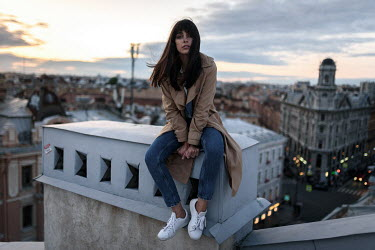 Ulyana Naydenkova BRUNETTE GIRL SITTING ON CITY ROOFTOP AT DUSK Women