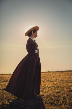 Joanna Czogala HISTORICAL WOMAN IN HAT IN COUNTRYSIDE AT SUNSET Women