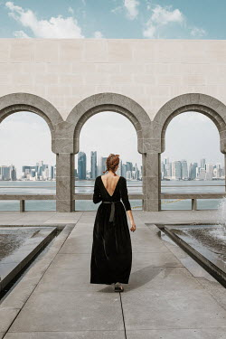 Nina Masic WOMAN WALKING BY ARCHES WITH RIVER AND CITYSCAPE Women