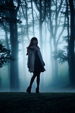 Nic Skerten GIRL STANDING IN FOGGY FOREST AT DUSK Women
