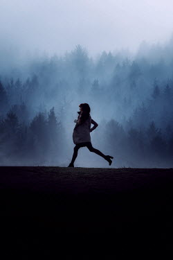 Nic Skerten WOMAN RUNNING BY FOGGY FOREST AT DUSK Women