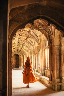 Rebecca Stice WOMAN WITH RED HAIR WALKING IN HISTORICAL PASSAGEWAY Women