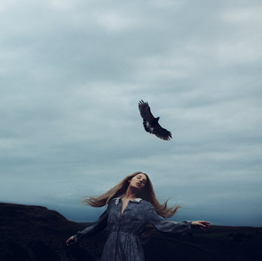 Rosie Hardy WOMAN WITH FLYING BIRD IN COUNTRYSIDE AT DUSK Women