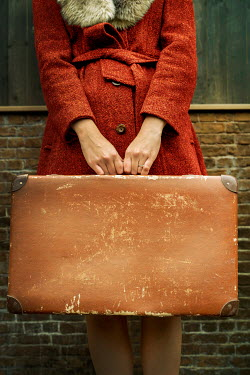 Stephen Mulcahey WOMAN IN COAT HOLDING WEATHERED SUITCASE Women
