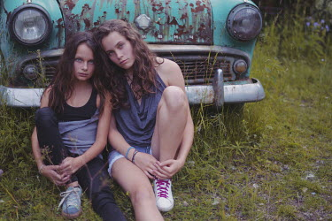 Anna Rakhvalova TWO SAD GIRLS SITTING BY RUSTY CAR Children