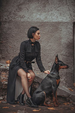 Hellen GIRL IN BLACK SITTING OUTDOORS WITH DOG Women