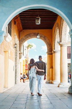 Eve North COUPLE WALKING ARM IN ARM IN COLONNADE  ON VACATION Couples