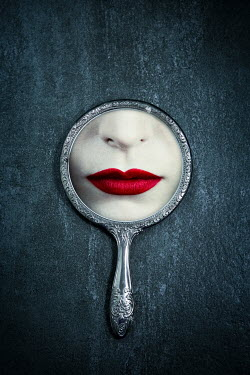 Magdalena Russocka woman's red lips reflected in old hand mirror