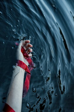 Magdalena Russocka womans hand with red ribbon in water