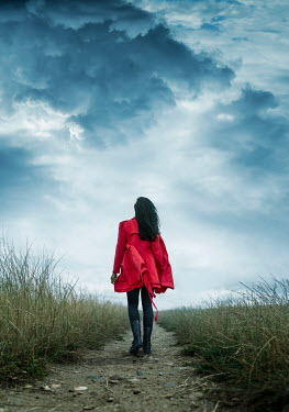 Stephen Mulcahey A woman wearing a red coat walking along a country path