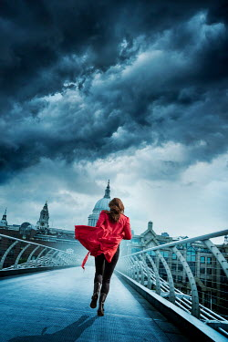 Stephen Mulcahey A woman wearing a red coat  running across  a bridge in london
