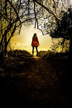 Stephen Mulcahey a woman wearing a orange coat walking near the edge of a wood