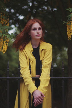 Anna Rakhvalova Young woman in yellow coat by fence