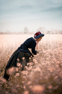 Ildiko Neer Victorian woman watching flowers in field