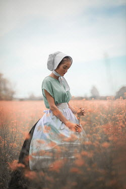 Ildiko Neer Historical servant holding flowers in field