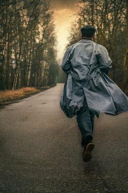 Jaroslaw Blaminsky Young man in gray coat walking on road