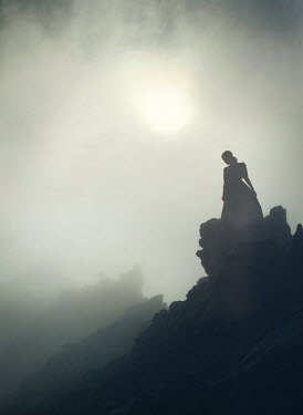 Mark Owen Silhouette of young woman standing on rock