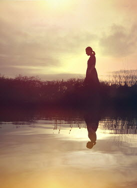 Mark Owen Silhouette of young woman walking by lake