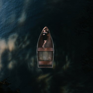 Rosie Hardy Young woman lying in boat on lake from above