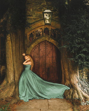 Rosie Hardy Young woman in blue dress standing at door between trees