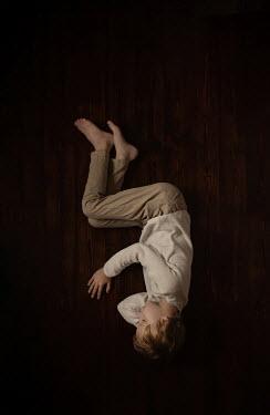 Sveta Butko Boy lying on wooden floor from above