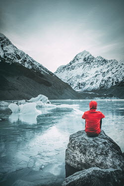 Evelina Kremsdorf Young woman in red jacket sitting on rock by Mount Cook and frozen lake in New Zealand