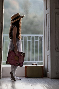 Nikaa Girl with book and suitcase by window