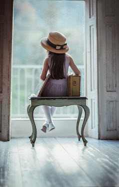 Nikaa Girl with suitcase sitting on bench by window