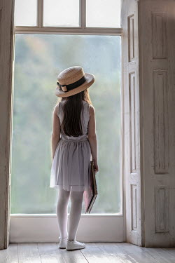 Nikaa Girl with sun hat and book by window