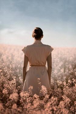 Ildiko Neer Brown hair woman standing in flower field