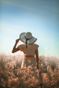 Ildiko Neer Woman in sun hat standing in flower field
