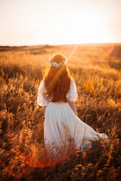 Rebecca Stice Young woman with daisy crown and white dress at sunset