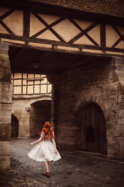 Rebecca Stice Young woman in dress walking under gate