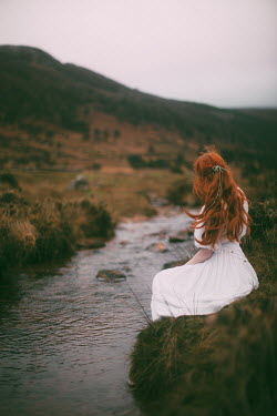 Rebecca Stice Young woman in white dress sitting on riverbank