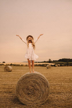 Rosie Hardy Young woman with arms raised on hay bale