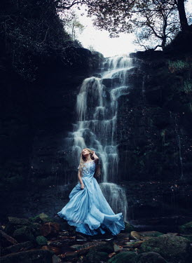 Rosie Hardy Young woman in blue dress by waterfall