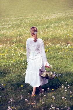 Carmen Spitznagel WOMAN IN WHITE CARRYING BASKET OF FLOWERS IN MEADOW Women