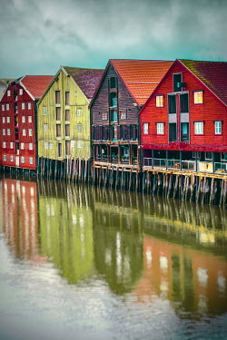 Des Panteva WOODEN BUILDINGS ON STILTS REFLECTED IN WATER Houses