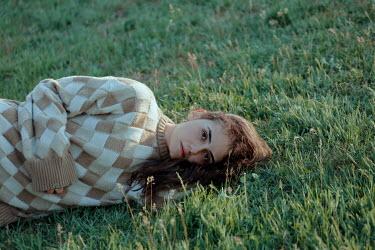 Felicia Simion SAD WOMAN IN SWEATER LYING ON GRASS Women