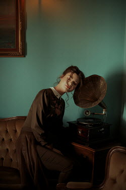 Felicia Simion BRUNETTE WOMAN LISTENING TO GRAMOPHONE INDOORS Women