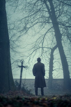Magdalena Russocka man standing by grave in foggy woods