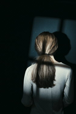 Magdalena Russocka young woman in dark room with window shadow