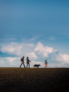 Mary Wethey YOUNG FAMILY WALKING DOG IN FIELD Groups/Crowds