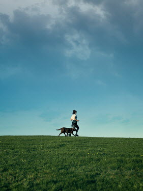Mary Wethey WOMAN RUNNING IN FIELD WITH DOG IN SUMMER Women