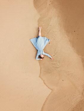 Rekha Garton WOMAN IN DRESS LYING ON SANDY BEACH Women