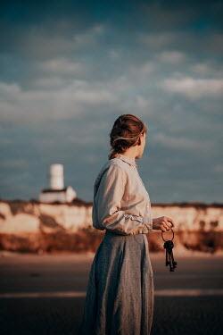 Rekha Garton WOMAN WITH KEYS ON BEACH WATCHING LIGHTHOUSE Women
