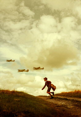 Stephen Mulcahey A boy running along  a road chasing planes